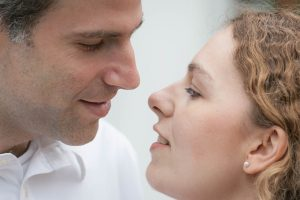 Man inwhite shirt moving in to kiss brunette with pearl earrings.