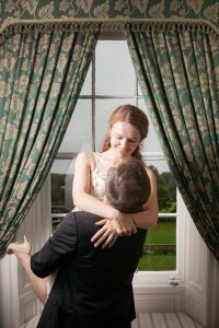 Man in jeans, jacket and white shirt lifts aloft his  brunette fiancée in white floral dress at a window of Bartley Lodge New Forest Hotel.