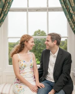 Man in jeans, jacket and white shirt and brunette fiancée in white floral dress exchanging loving looks at window of Bartley Lodge New Forest Hotel.