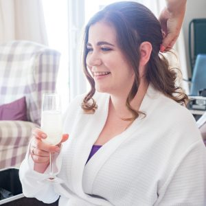 Bride enjoys glass of prosecco while her har is styled for her wedding