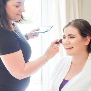 Make-up artist applies blusher to smiling bride before her wedding