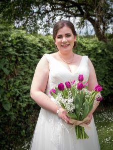 Smiling bride in wedding dress and pearl necklace holding bouquet of purple tulips