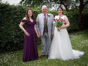 Bride, bridesmaid and father before  classic English country church wedding