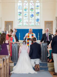 Vicar blesses couple kneeling before altar durng classic English country church wedding