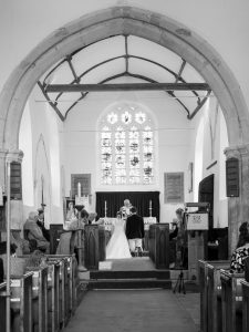 Bride and groom kneel before altar during  classic English country church wedding