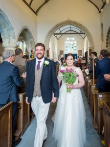 Bride and groom walk down aisle at end of  classic English country church wedding service
