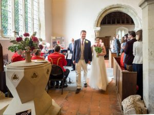 Bride and groom walk down aisle at end of  classic English country church wedding service as brass band plays