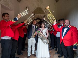 Brass band in red jackets form guard of honour for bride and groom in English country church porch