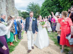 Guests throw confetti over bride and groom in churchyard  after classic English country church wedding