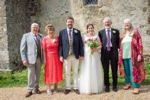 Bride , groom and their parents in family portrait after classic English country church wedding