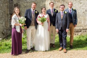 Bride groom, bridesmaid, best man and ushers after  classic English country church wedding