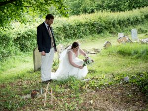Bride lays bouquet on grave of grandparent after classic English country church wedding