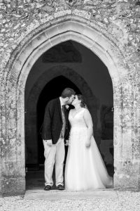 Monchrome portrait of bride and groom framed by English country church porch