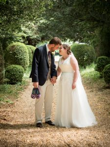 Bride and groomenjoy romantic moment on yew-lined gravel path after classic English country church wedding