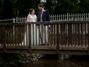 Bride and grrom smile at each other on bridge over stream after classic English country church wedding