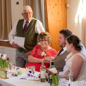 Father of bride giving speech as  mother, bride and groom look on