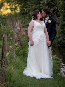 Bride and groom kiss next to a country stream