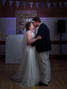 Bride and groom kiss during first dance at wedding reception
