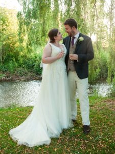 Romantic portrait of bride and groom by stream lit by sun shafting through weeping willow