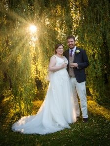 Romantic portrait of bride and groom lit by sun rays shafting through weeping willow