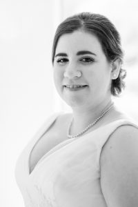 Monochrome portrait of smiling bride wearing wedding dress and pearl jewellery