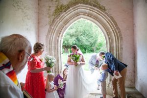 Bride and bridal party in English country church porch just before wedding service