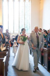 Bride and father walk up aisle at start of classic English country church wedding