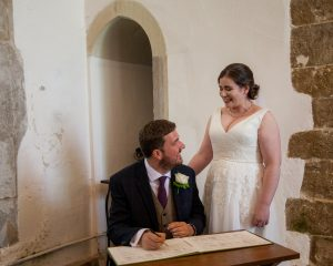 Standing bride smiles at seated groom singing register classic English country church wedding