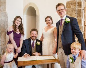 Seated groom with bride, bridesmaids, best man and marriage register during classic English country church wedding