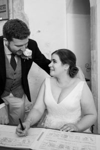 Groom looks on as bride signs register during classic English country church wedding