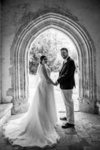 Monochrome portrait of bride and groom in porch of English country church after wedding