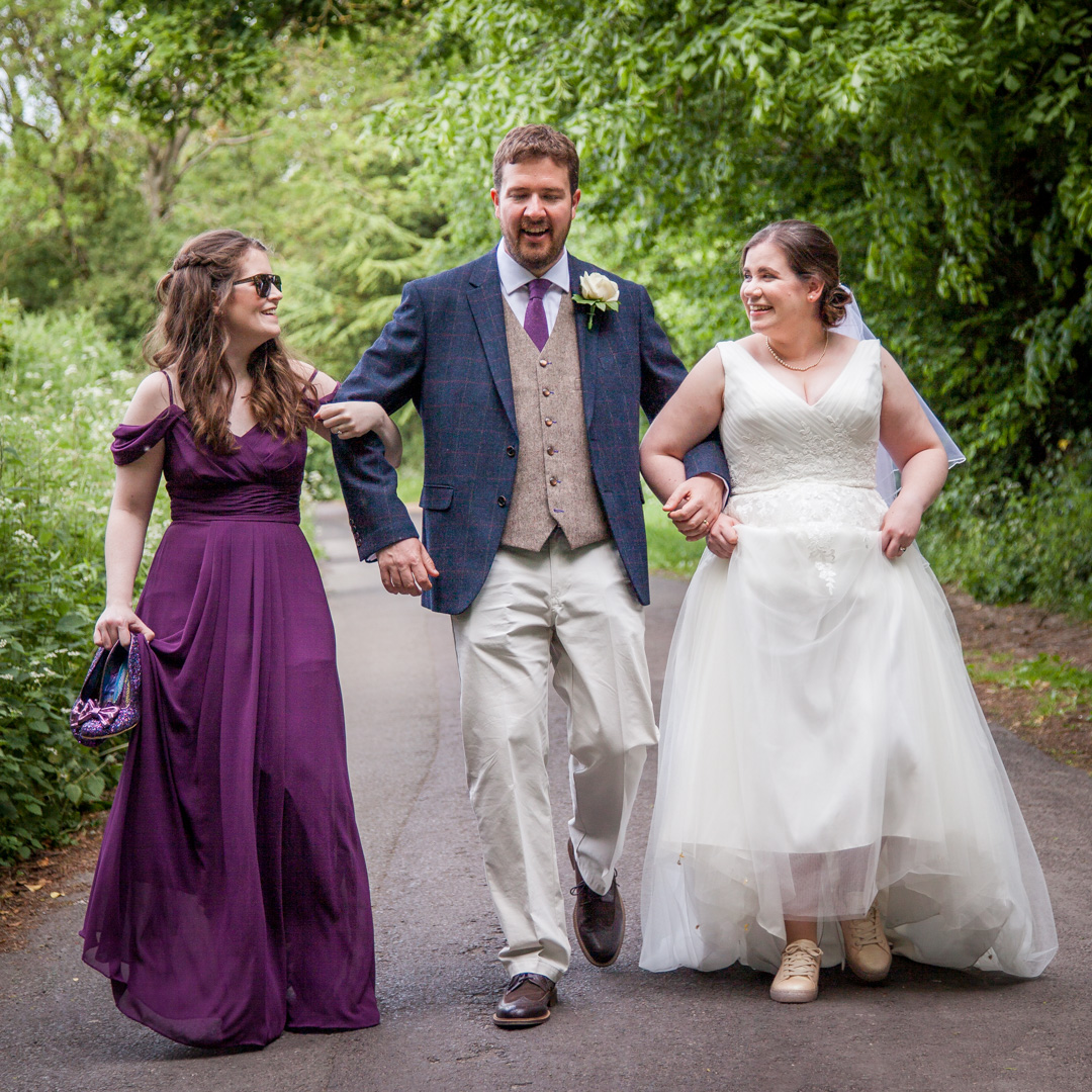 Bride, groom and bridesmaid walk together down English country lane after wedding