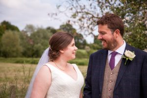 Bride and groom smile at each other after classic English country church wedding