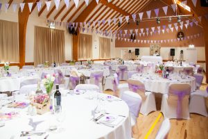 Tables laid for purple-themed wedding reception in village hall