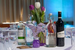 Purple-themed table decorations detail at wedding reception