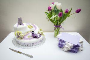 Dinosaur-thmed wedding cake, purple tulips, napkin and cake knife on white table at wedding reception