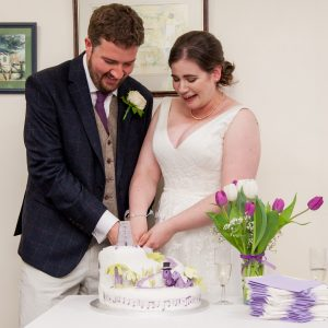 Bride and groom smile as they cut dinosaur-themed wedding cake during reception