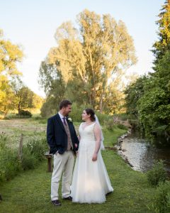 Bride and groom smile at each other in romantic portrait beside country stream