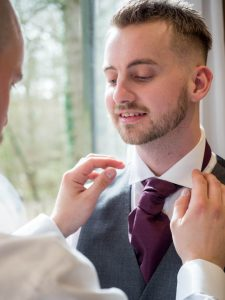 Best man adjusts tie of bridegroom