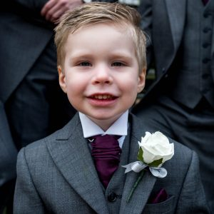 Little boy in morning suit standing in front of groomsmen