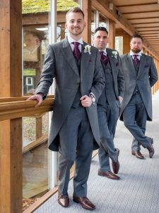 Groomsmen pose in corridor at Marwell Hotel