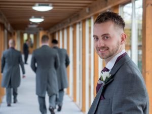 Bridegroom poses in corridor at Marwell Hotel