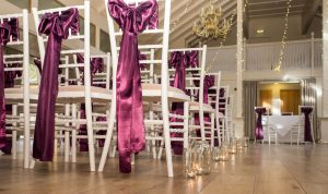Dark burgundy ribbons adorn white chairs set out for wedding at Marwell Hotel