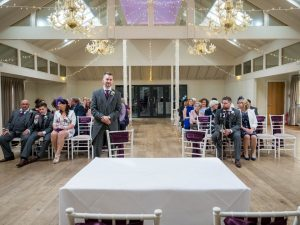 Bridegroom poses in front of guests in wedding ceremony hall at Marwell Hotel