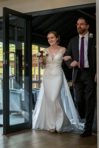 Bride enters with father at wedding cereomny in Marwell Hotel