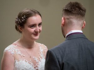 Bride smiles at groom during wedding ceremony