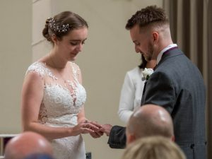 Bride puts ring on groom's left finger during wedding at Marwell Hotel