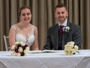 Bride and groom smile after signing registers at their wedding at Marwell Hotel