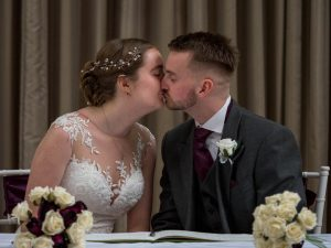 Bride and groom kiss after signing registers at their wedding at Marwell Hotel