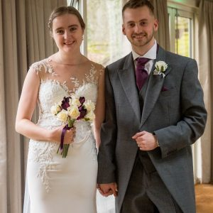 Bride and groom smile after walking down the aisle at their wedding at Marwell Hotel